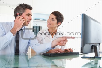 Close up of a man showing something to his coworker on a computer