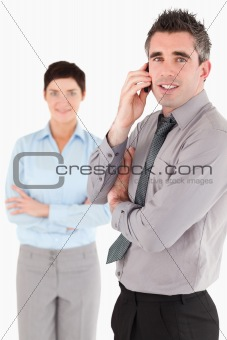 Portrait of a man making a phone call while his colleague is posing