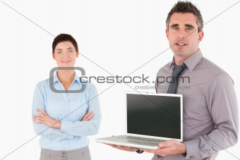 Office worker showing a laptop while his colleague is posing
