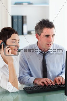 Portrait of a woman telephoning while her colleague is using a computer