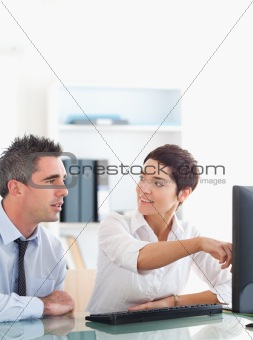 Woman pointing at something to her colleague on a screen