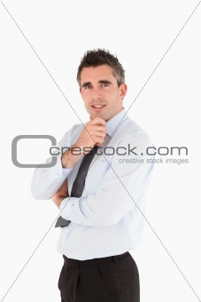 Portrait of a smiling salesperson with his hand on his chin