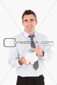 Man putting a bank note in a piggy bank