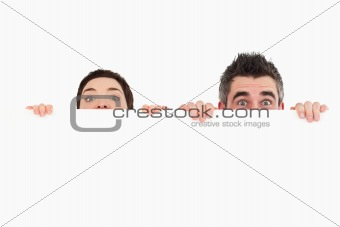 Man and woman hiding behind a white board with room for  copy space