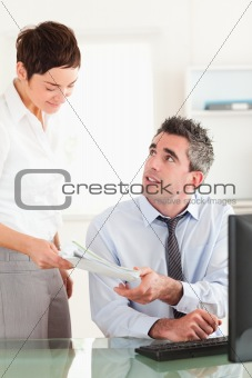 Portrait of secretary giving a document to her manager