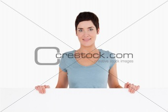 Woman standing behind a blank panel