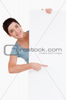 Smiling brunette pointing at a blank panel