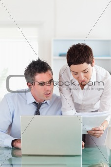 Portrait of colleagues comparing a blueprint document to an electronic one