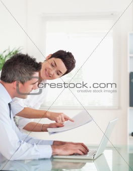 Portrait of coworkers comparing a blueprint folder to an electronic one