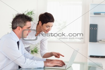 Woman pointing at something to her colleague on a laptop