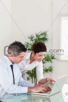 Portrait of a woman pointing at something to her colleague on a laptop