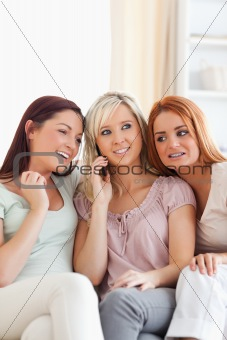 Charming women sitting on a sofa with a mobile