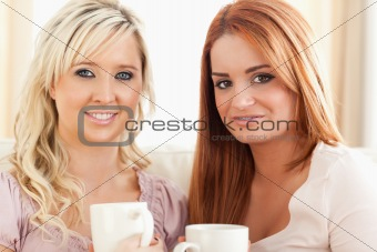 Young Women sitting on a sofa with cups