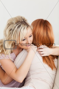Hugging cute women sitting on a sofa
