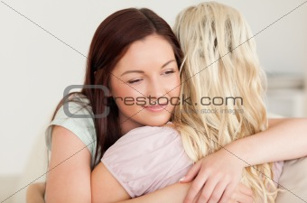 Happy women hugging on a sofa