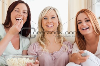 Charming Friends lounging on a sofa watching a movie