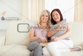 Joyful women lounging on a sofa watching a movie