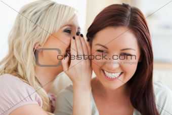 Cute woman telling her best friend a secret