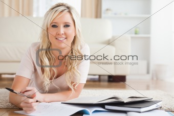 Blond smiling College Student lying on the floor learning