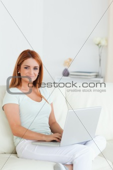 Charming woman sitting on a sofa with a notebook