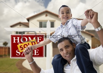Happy Hispanic Father and Son in Front of New House and Sold Real Estate Sign.