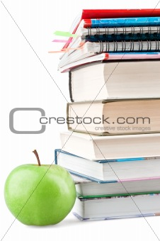 Textbooks and notebooks next to the green apple