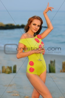 Beautiful woman with glass of champagne dancing on the beach in lime color designer's swimsuit