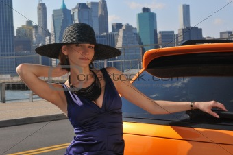 Young sexy girl posing in enening dress and hat by metallic orange sport car