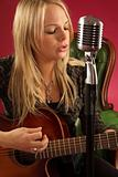 Blond female playing acoustic guitar