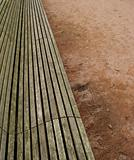 long wooden plank bench on orange gravel