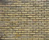 worn dirty yellow brick wall