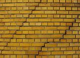 yellow brick wall with 2 large cracks