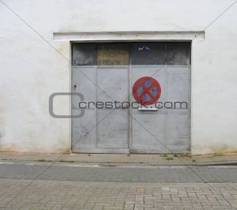 gray grungy metal garage door with side-walk