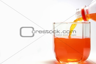 Pouring orange beverage.