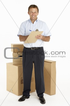 Portrait Of Courier Standing Next To Parcels, Holding A Clipboar