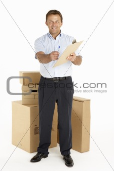 Portrait Of Courier Standing Next To Parcels, Holding A Clipboard
