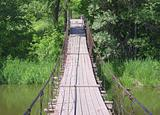 Old suspension walk bridge across river in the  forest