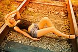Beautiful young girl lying on rails