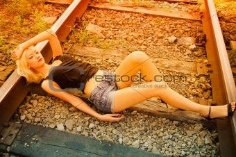 Beautiful young girl lying on rails