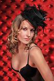 Portrait of beautiful Lingerie model wearing black stockings,lingerie and hat on studio red satin background