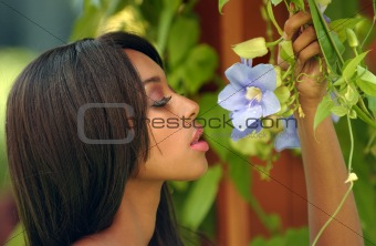 Portrait of beautiful African American woman enjoying spring flowers in the garden