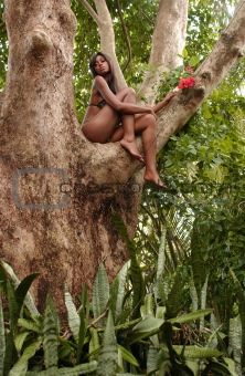 Portrait of beautiful African American woman sitting on the tree and enjoying spring flowers in the tropical forest