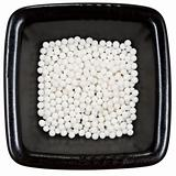 sugar homeopathy balls on black plate close up