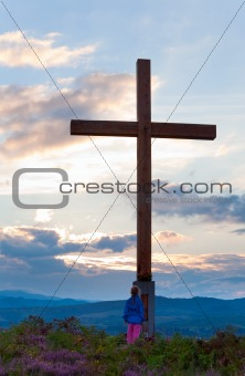 Small girl near wooden cross on summer heather flower hill top