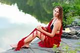 Beautiful woman wrapped a red shawl on the coast pond