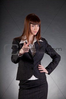 Serious looking business woman pointing in camera