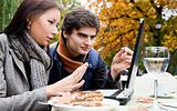 Couple sitting laptop park