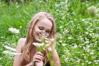 young girl in a meadow with camomiles