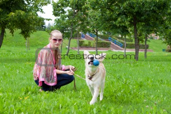 girl playing in the park with a puppy