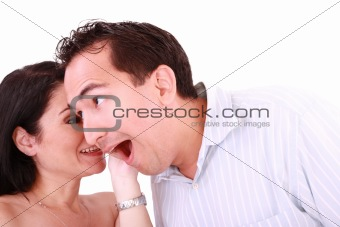girl tells something into surprised guy's ear isolated on white